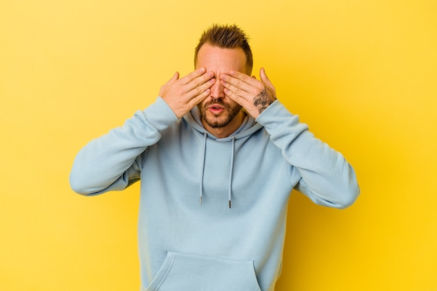 Jovem tatuado homem caucasiano isolado no fundo amarelo com medo de cobrir os olhos com as mãos.