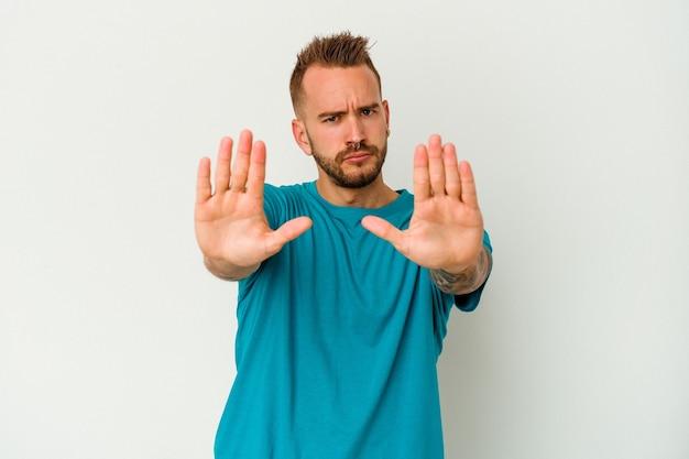 Jovem tatuado homem caucasiano isolado no fundo branco, de pé com a mão estendida, mostrando o sinal de stop, impedindo você.