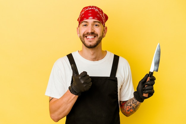 Jovem tatuado homem caucasiano segurando uma faca isolada na parede amarela, sorrindo e levantando o polegar
