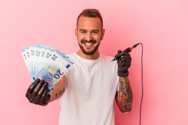 Jovem tatuador caucasiano segurando notas isoladas em um fundo rosa