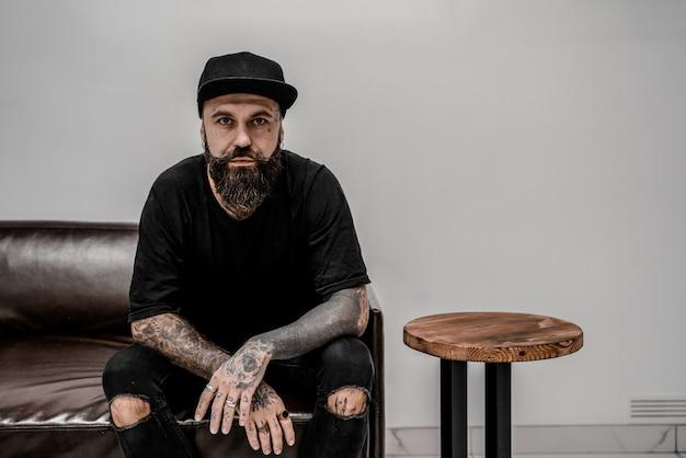 Jovem tatuador masculino com barba parece sério, sentado no sofá no local da oficina.