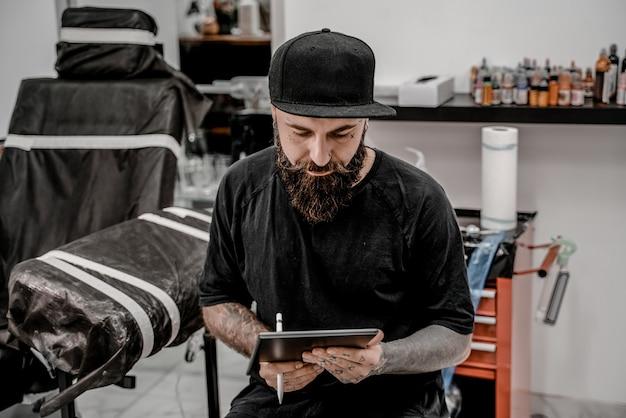 Jovem tatuador masculino com barba segurando o lápis e o esboço, parecendo positivo e feliz em pé e sorrindo no local da oficina.