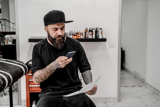 Jovem tatuador masculino com barba tirando foto do esboço sentado no sofá no local da oficina.