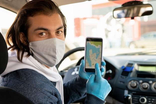 Jovem taxista com máscara protetora e luvas apontando para a tela do smartphone