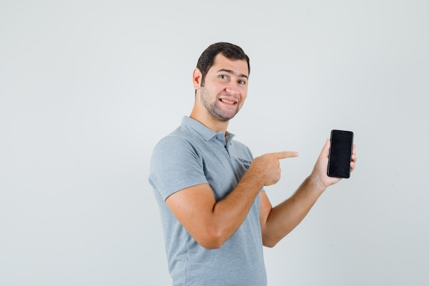 Jovem técnico de uniforme cinza, apontando para o celular e olhando alegre, vista frontal.