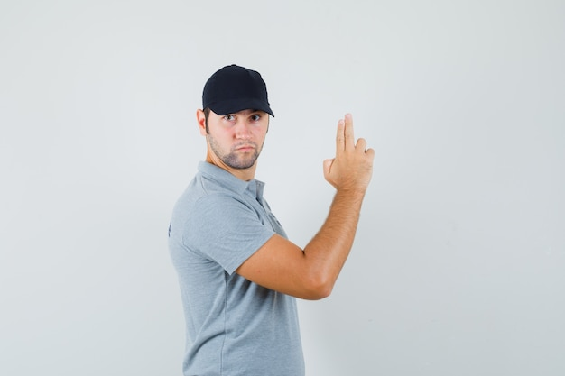 Jovem técnico de uniforme cinza fazendo sinal de pistola de dedo e parecendo estrito.