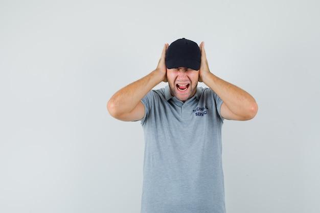 Jovem técnico de uniforme cinza, mantendo as mãos nas orelhas e parecendo irritado.