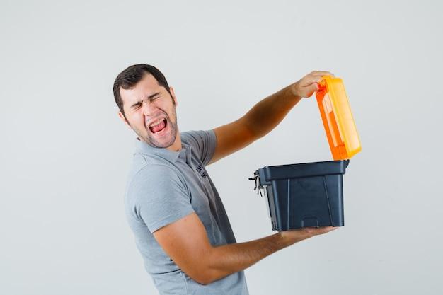 Jovem técnico de uniforme cinza segurando a caixa de ferramentas aberta e parecendo enojado.