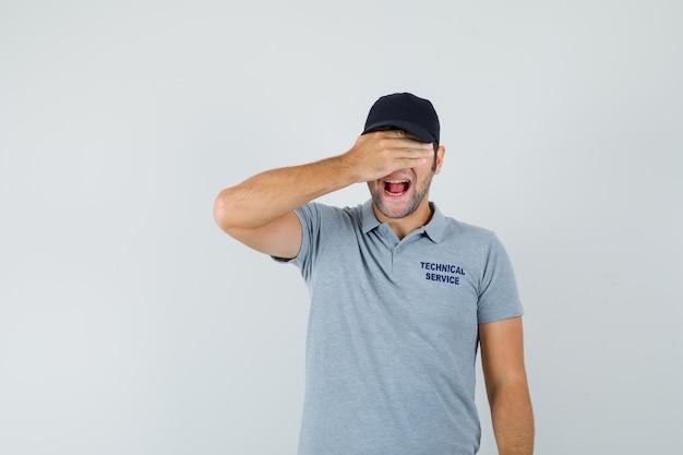 Jovem técnico de uniforme cinza, segurando a mão nos olhos e parecendo animado.