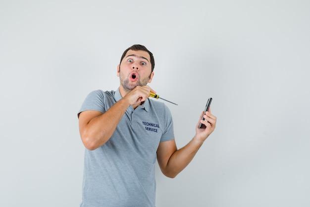 Jovem técnico de uniforme cinza segurando uma chave de fenda e tentando abrir a parte de trás do telefone e parecendo atordoado