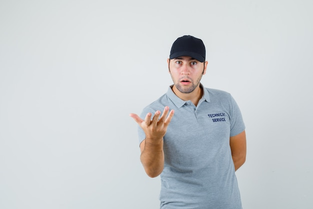 Jovem técnico, esticando a mão em um gesto perplexo na vista frontal uniforme cinza.