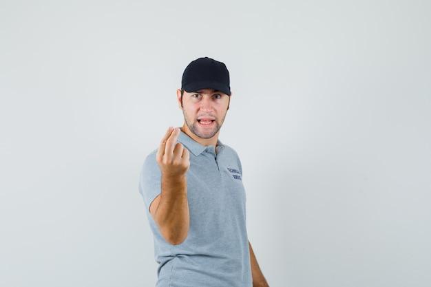 Jovem técnico fazendo gesto italiano em uniforme cinza e parecendo nervoso.