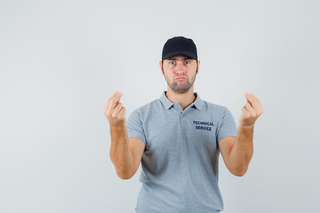 Jovem técnico fazendo gesto italiano em uniforme cinza e parecendo perplexo.