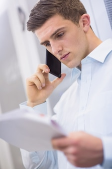 Jovem técnico ligando e lendo um documento