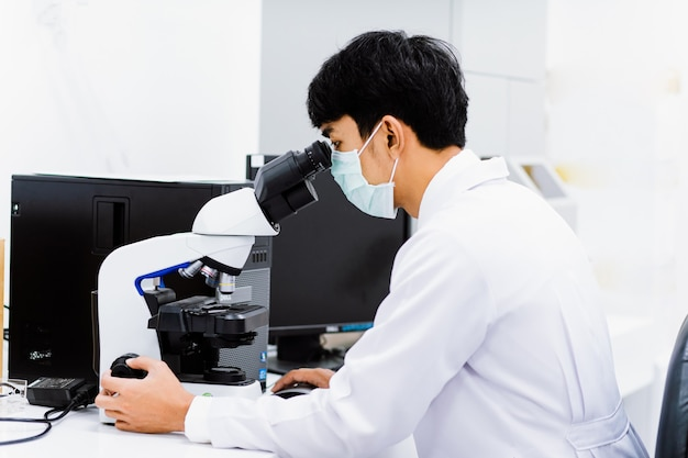 Jovem técnico médico olha para o microscópio no laboratório médico