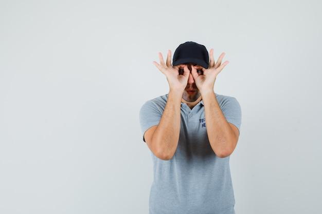 Jovem técnico mostrando gesto de óculos em uniforme cinza e olhando curioso.