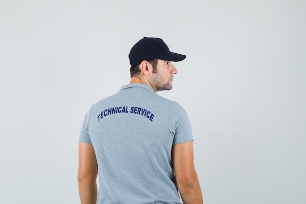 Jovem técnico olhando de lado em uniforme cinza e olhando focado, vista traseira.