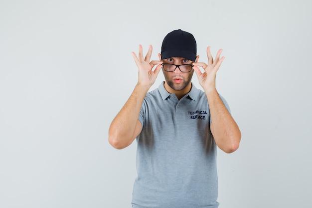 Jovem técnico olhando por cima de óculos em uniforme cinza e parecendo surpreso.