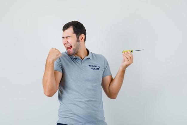 Jovem técnico segurando a chave de fenda em uniforme cinza e parecendo feliz.