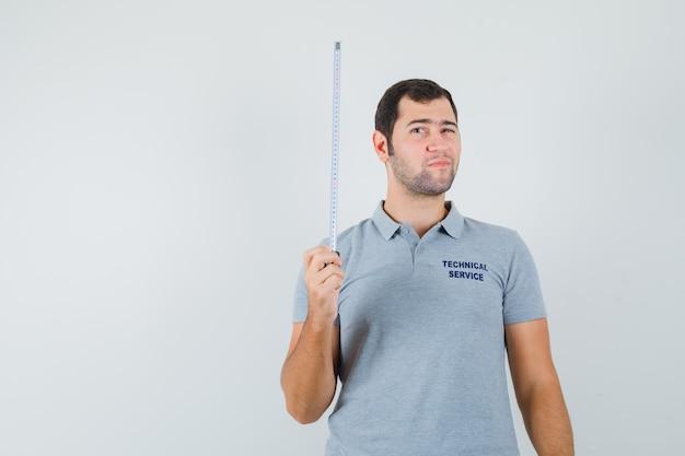 Jovem técnico segurando a fita métrica com uma mão em uniforme cinza e olhando sério.