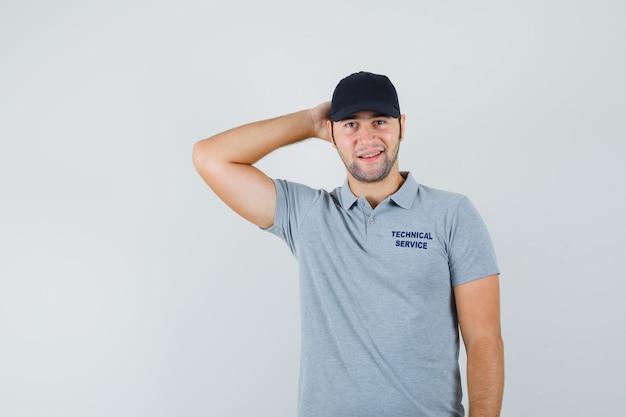 Jovem técnico segurando a mão atrás da cabeça em uniforme cinza e elegante.