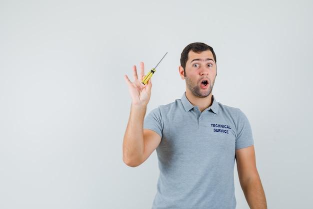 Jovem técnico segurando chaves de fenda em uma mão em uniforme cinza e parecendo surpreso.