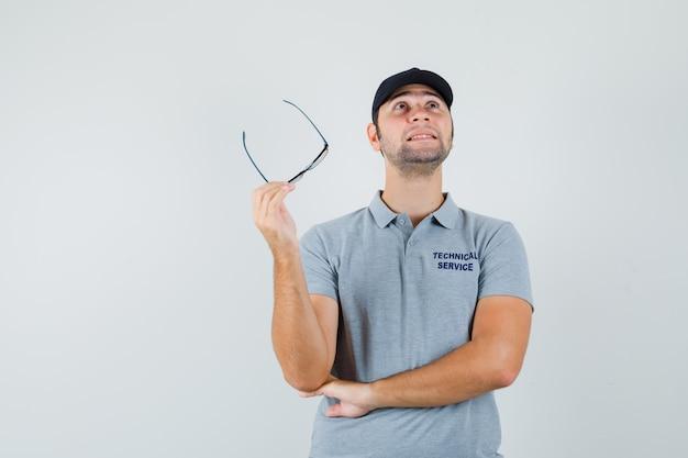 Jovem técnico segurando óculos de uniforme cinza e parecendo pensativo.