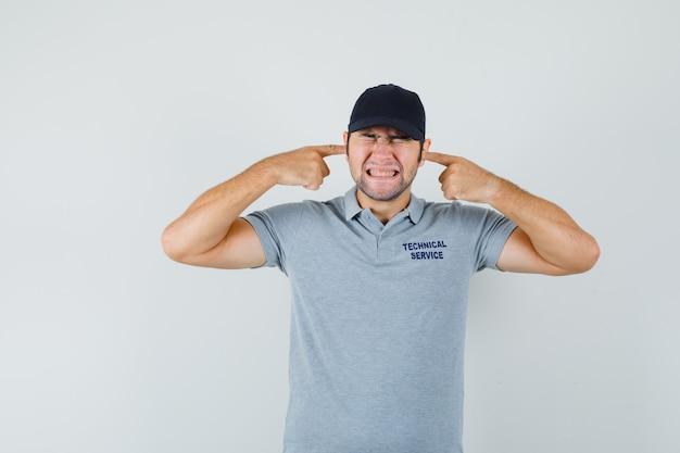 Jovem técnico tapando os ouvidos com os dedos em uniforme cinza e parecendo irritado.