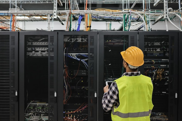 Jovem técnico trabalhando com tablet dentro de uma sala de big data center cheia de servidores em rack - foco na cabeça do homem