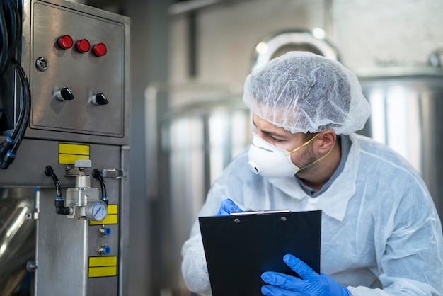 Jovem tecnólogo em uniforme protetor branco, controlando a máquina industrial na planta de produção