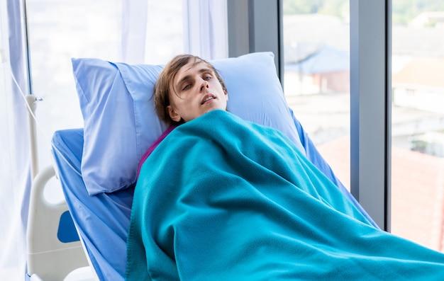 Jovem tem calafrios de febre, paciente encontra-se na cama de seus tremores no fundo do quarto do hospital.