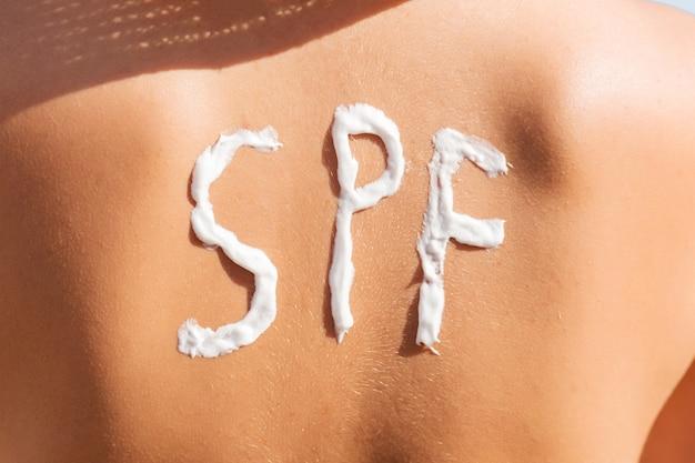 Jovem tem spf palavra nas costas feita de protetor solar