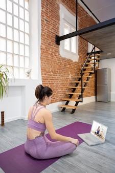 Jovem, tendo uma aula de ioga online em seu laptop. ela está aprendendo em casa. espaço para texto.