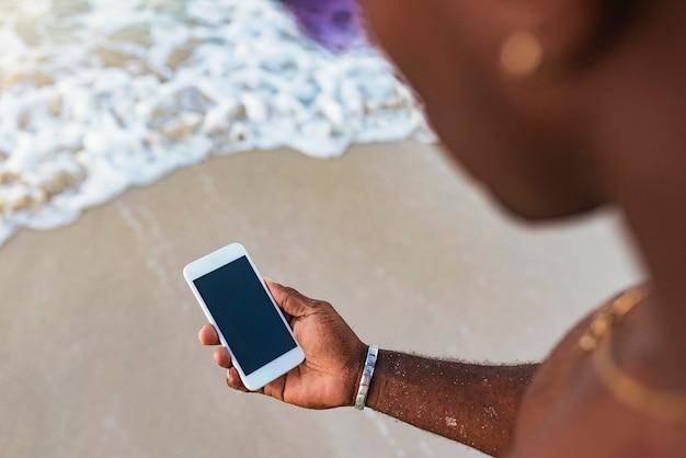 Jovem tendo usando seu celular na praia. conceito móvel.