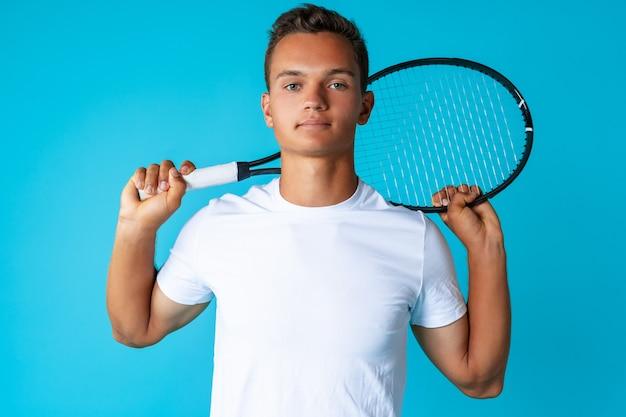 Jovem tenista em roupas esportivas posando contra um fundo azul close-up