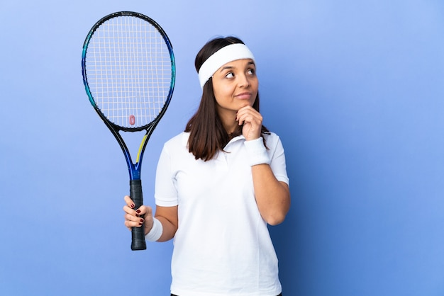 Jovem tenista em uma parede isolada pensando em uma ideia enquanto olha para cima