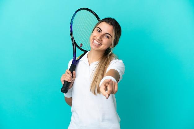 Jovem tenista isolada em um fundo azul apontando para a frente com uma expressão feliz