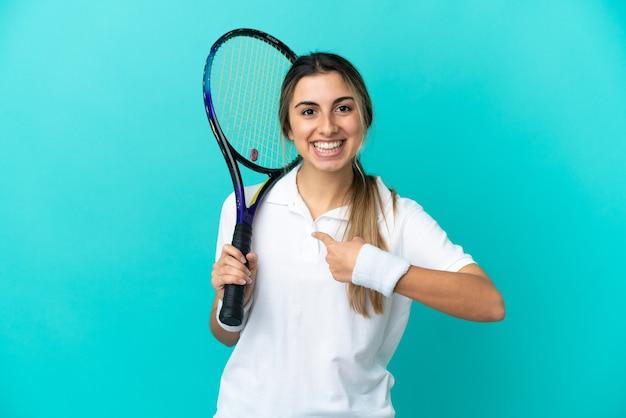 Jovem tenista isolada em um fundo azul com expressão facial surpresa