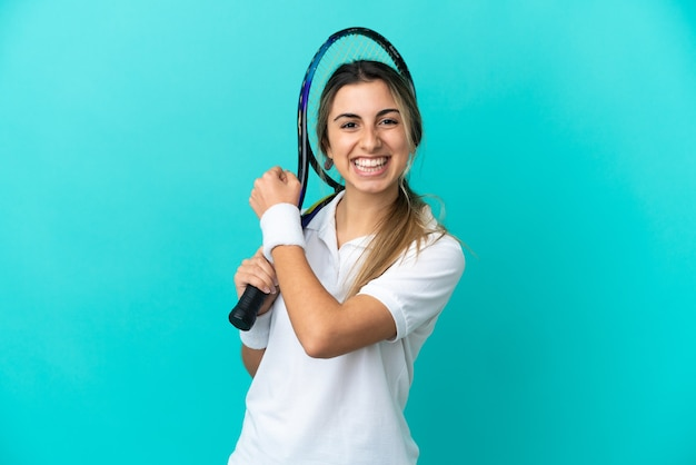 Jovem tenista isolada em um fundo azul comemorando uma vitória