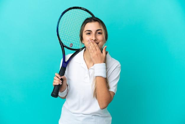 Jovem tenista isolada em um fundo azul feliz e sorridente, cobrindo a boca com a mão