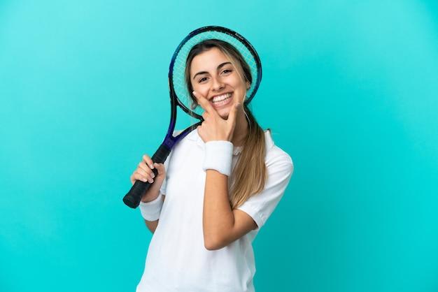 Jovem tenista isolada em um fundo azul feliz e sorridente