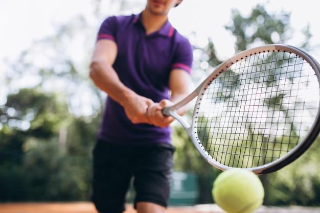 Jovem tenista na quadra, raquete de tênis close-up