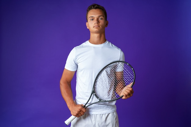 Jovem tenista posando com uma raquete de tênis contra um fundo roxo