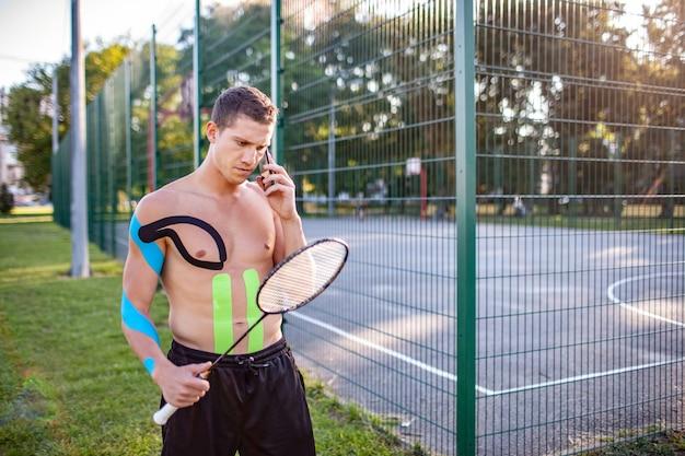 Jovem tenista profissional, caucasiano, com cinesiologia, gravando o corpo carregando uma raquete perto de um campo esportivo cercado