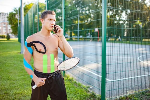 Jovem tenista profissional, caucasiano, com cinesiologia, gravando o corpo com a raquete perto de um campo esportivo cercado
