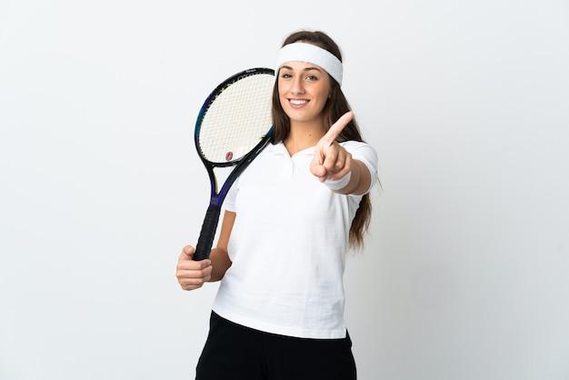 Jovem tenista sobre fundo branco isolado, mostrando e levantando um dedo