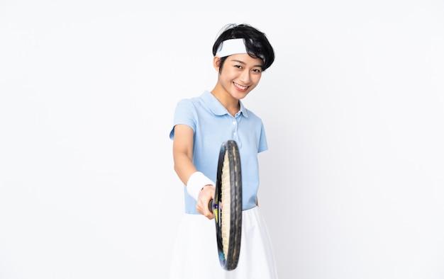 Jovem tenista vietnamita mulher sobre parede branca jogando tênis