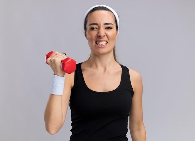 Jovem tensa e bem esportiva usando bandana e pulseiras levantando halteres isolado na parede branca com espaço de cópia