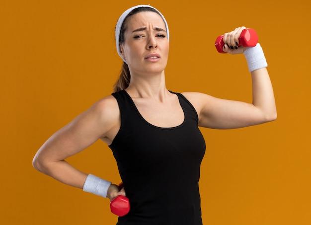 Jovem tensa, muito desportiva, usando bandana e pulseiras, segurando e levantando halteres, mantendo a mão na cintura isolada na parede laranja