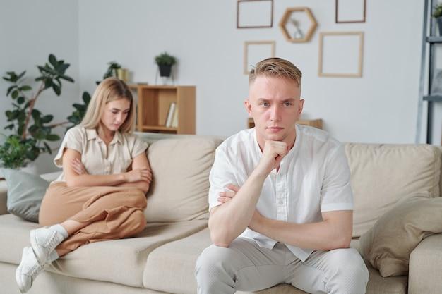 Jovem tenso com expressão facial chateada, sentado no sofá no fundo de sua esposa infeliz com os braços cruzados no peito